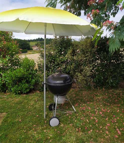 Un barbecue sous un parasol pour se protéger de la pluie.